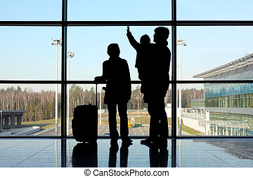 silhouette of young family with luggage standing near window...