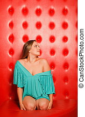 woman in a turquoise dress sitting on red leather couch...