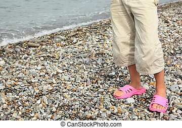 coast of sea. legs of child with slippers. focus on right footstep.