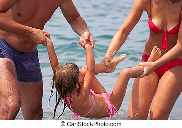 young family bathes in sea. wet happy daddy and mum play with daughter standing in water