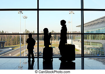 silhouette of mother, son and daughter with luggage standing near window in airport