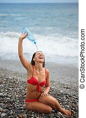 one joyful woman wearing swimsuit with bottle is sitting near water on sea coast
