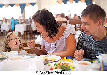young caucasian family having dinner together. mother,...