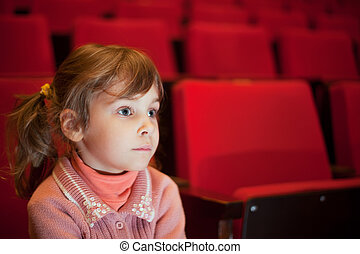 little girl sitting on armchairs at cinema, steadfastly...