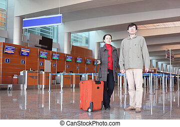man and girl with red suitcase standing in airport hall looking at camera