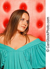 woman in a turquoise dress, near to a red wall. flowing...