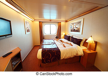 little boy lies on big double bed in ship cabin general view summer day