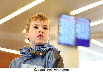 portrait of little boy in airport looking into the distance blue screens on background