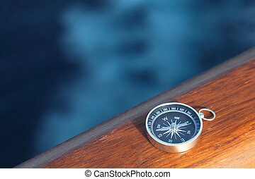 little cruise compass on wooden rail sea on background