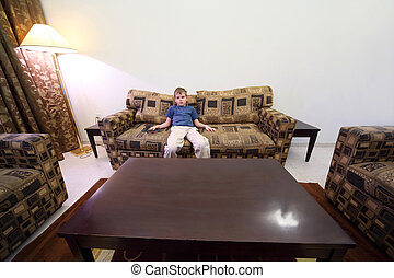 little boy with remote control sitting at brown sofa in room with white walls and watching tv general view
