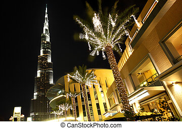 night Dubai street, palms with decor lamps and Burj Dubai,...