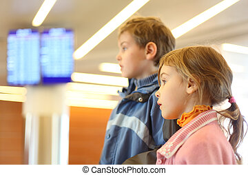 little boy and girl in airport blue screens on background side view half body