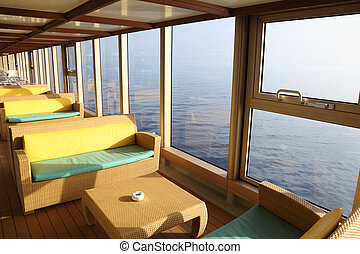 room for rest with sofas and tables near window in cruise...