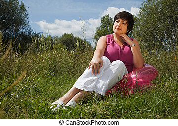 woman in summer day rest in the open air sitting on an inflatable armchair. think about