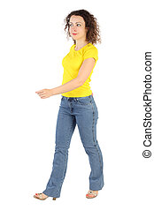 tractive woman in yellow shirt and jeans walking left...