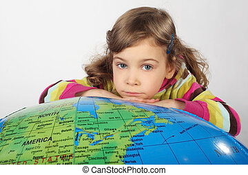 little girl lies on big inflatable globe, chin on hands, looking at camera
