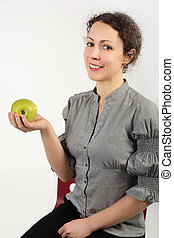 young attractive woman holding an apple in one hand, looking at camera, vertical