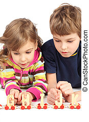 little boy and girl playing with wooden railway, lying on...