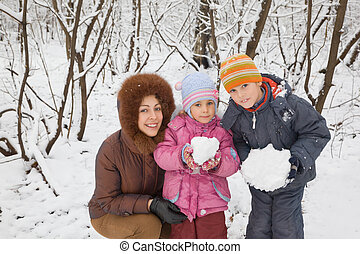 young woman with boy and little girl in winter in wood,...