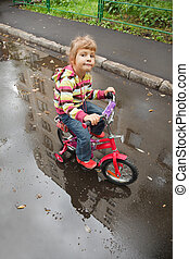 little girl goes on a bicycle on wet asphalt, reflexion in puddle