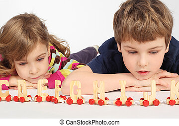 little boy and girl lying on floor and playing with wooden alphabet railway, focus on boy