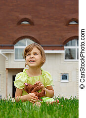 little girl sitting on lawn in front of new home In her...