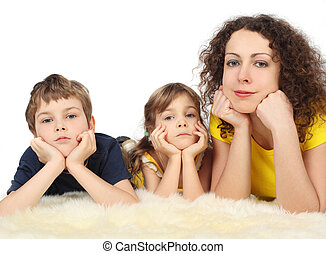 mother with two serious children lies on white fell studio...