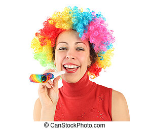young beauty woman in clown wig and with party blower, laughing and looking at camera