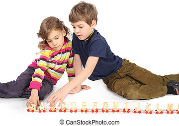 little boy and girl playing with wooden railway sitting on floor isolated on white, horizontal