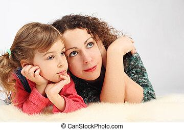 little girl and her mother lies on white fell, hands on chin,looking at side