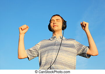 one handsome man is listening music outdoors with closed eyes.