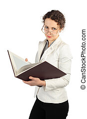 young serious woman in glasses holding big book, looking at...