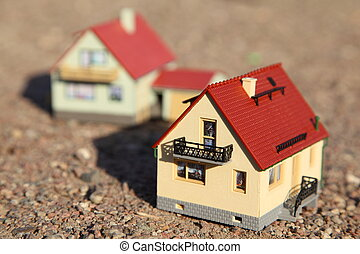 two small models of houses. front model of house in focus.
