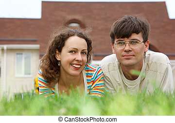 Guy with girl lying on lawn in front of new home. Smiling look into camera.