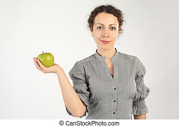 young attractive woman holding an apple in one hand, looking at camera, horizontal