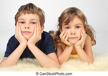 little boy and girl lying on white fell, chin on hands, looking at camera