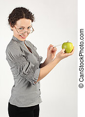 young attractive woman in business dress holding an apple and pointing on it for a pen, looking at camera