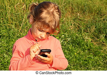 little girl is sitting on a grass of meadow with communicator.