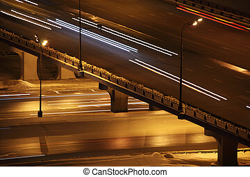 night city with bridge and lighting columns road traffic with trace of cars