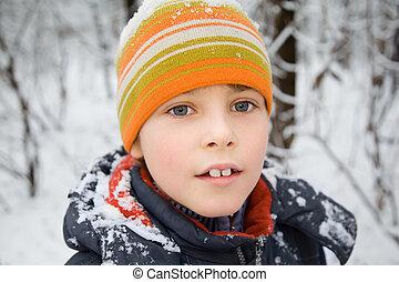boy in cap with snow on shoulders in wood in winter