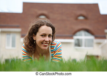 Happy girl on lawn in front of new home. Smiling, she looks into camera. Horizontal format. Close-up.