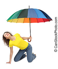 young attractive woman in yellow shirt with multicolored umbrella sitting isolated on white and looking up