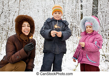 young woman with boy and little girl with Bengal fires in hands in winter in wood