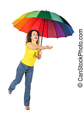 young beauty woman in yellow shirt with multicolored umbrella jumping with reached out a hand isolated on white