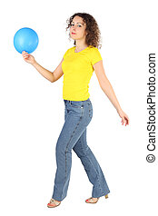 young attractive woman in yellow shirt and jeans with blue balloon walking left isolated on white