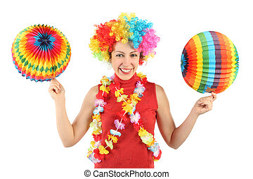 young beauty woman in clown wig, flower garland and multicolored decorative balls, smiling and looking at camera, half body