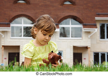 little girl sitting on lawn in front of new home. In her...