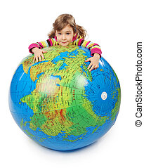 little girl look out of big inflatable globe and embracing it, isolated on white