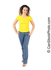 young attractive woman in yellow shirt and jeans standing,...