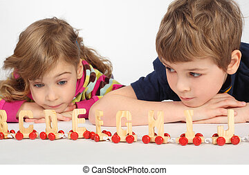 little boy and girl lying on floor and playing with wooden alphabet railway, focus on boy, boy looking at gir